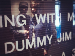 Jez and Polly relected in cinma window with Dummy Jim listing